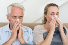 Sick couple blowing their noses sitting on the couch Stock Image