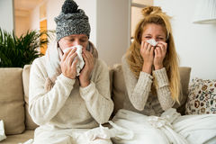 Sick couple catch cold. Man and women sneezing, coughing, got flu, having runny nose. Spraying medication into nose and throat Royalty Free Stock Photography
