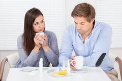 Sick couple drinking lemon tea at table Stock Photography