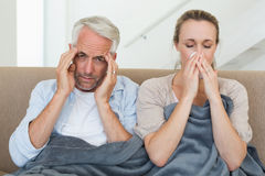 Sick couple sitting on the couch under a blanket Stock Images