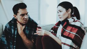 Sick Couple Sitting on Sofa in Checkered Blankets. Man at Home. Sick Young Woman. White Sofa in Room. Unhappy Guy. Disease Concept royalty free stock photos