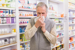 Sick customer sneezing on tissue Stock Photo