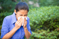 Sick day. Closeup portrait, young woman in blue shirt with allergy or cold, blowing her nose with a tissue, looking miserable unwell very sick, isolated outside Stock Photography
