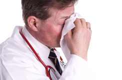 Sick doctor, sneezing. Also, a doctor can have a cold and need for treatment and care Royalty Free Stock Images