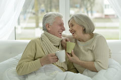 Sick  elderly couple in bed. Portrait of sick  elderly couple in bed with tea Royalty Free Stock Images