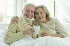 Sick  elderly couple in bed. Portrait of sick  elderly couple in bed with tea Stock Image