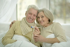 Sick  elderly couple in bed. Portrait of sick  elderly couple in bed with thermometer Royalty Free Stock Photo