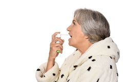 Sick elderly lady with inhaler. Ill senior lady with inhaler on white background Stock Images