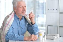 Sick elderly man makes inhalation Royalty Free Stock Photos