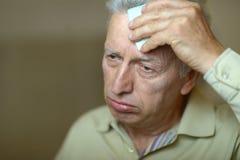 Sick elderly man. Portrait of a sick elderly man close up royalty free stock photo