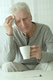 Sick elderly man. Portrait of sick elderly man with cup Royalty Free Stock Photos