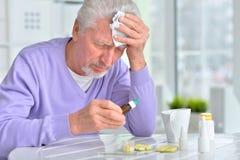 Sick elderly man taking medicine. Portrait of a sick elderly man taking medicine Royalty Free Stock Image