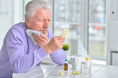Sick elderly man taking medicine. Portrait of a sick elderly man taking medicine Stock Photos