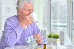 Sick elderly man taking medicine. Portrait of a sick elderly man taking medicine Stock Images