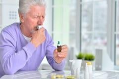 Sick elderly man taking medicine. Portrait of a sick elderly man taking medicine Stock Image