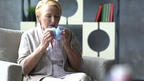 Sick elderly woman coughing and holding head on background of medicine drug in cup of water