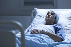 Woman alone in hospital bed. Sick, elderly woman with a headscarf and eyes closed dying alone of cancer in a hospital bed royalty free stock photography