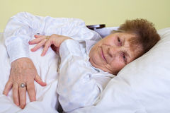 Sick elderly woman lying in bed Stock Photos