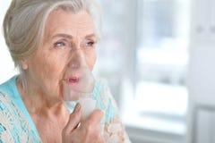 Sick elderly woman making inhalation. Portrait of a sick elderly woman making inhalation Royalty Free Stock Photos