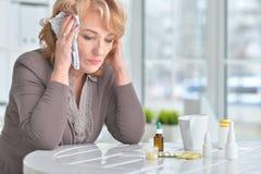 Sick elderly woman with medicines. Portrait of a sick elderly woman with medicines royalty free stock image