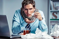 Sick employee takes pills for flu in the office. Photo of young man suffering virus of flu Royalty Free Stock Images