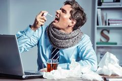 Sick employee using spray for throat. Photo of young man in office suffering virus of flu. Medical concept royalty free stock images