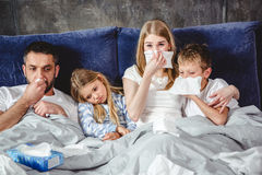Sick family on bed. Family of four has a flue and lying on bed together Royalty Free Stock Photography