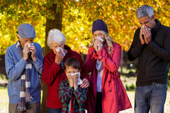 Sick family blowing their noses at park Stock Photo