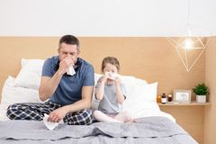 Sick father and daughter blowing their noses royalty free stock image