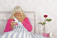 Sick female in bed looking worried at thermometer Stock Images