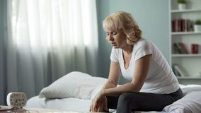 Sick female feeling headache, sitting on bed, migraine attack, stress discomfort. Stock photo royalty free stock image