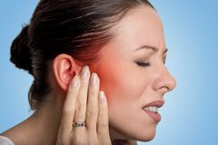 Sick female having ear pain touching her painful head. Tinnitus. Closeup up side profile sick female having ear pain touching her painful head isolated on blue Stock Photography