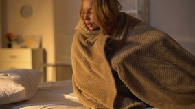 Sick female lying in bed covering with blanket, fever symptom, flu weakness. Stock footage stock video footage