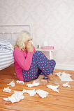 Sick female sitting next to bed Stock Images