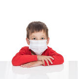 The sick five-year-old boy sits at a white table with medicine healthcare mask Stock Photo