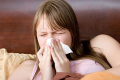 Sick with flu teenager girl in bed sneezing Stock Images