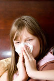 Sick with flu teenager girl in bed sneezing Stock Image