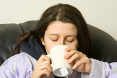 Sick girl. Woman with a cold drinking a hot tea Royalty Free Stock Images