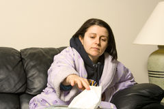 Sick girl. Woman with a cold reaching out for a tissue stock photos