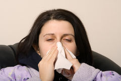 Sick girl. Woman with a cold blowing her nose with a tissue Stock Images