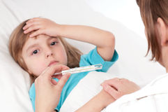 Sick girl. Sick little girl in bed. Mother with thermometer is sitting near the bed. Focus on thermometer Stock Images