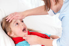 Sick girl. Sick little girl showing throat to the mother or doctor Royalty Free Stock Image