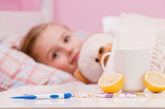 Sick girl in bed. Medicines and hot tea in front, sick girl with teddy bear in bed Royalty Free Stock Photos