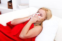 Sick girl blowing her nose Royalty Free Stock Photography