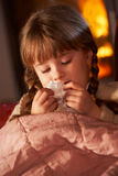 Sick Girl With Cold Resting On Sofa. By Cosy Log Fire Stock Photo
