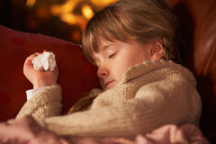 Sick Girl With Cold Resting On Sofa. By Cosy Log Fire Royalty Free Stock Image