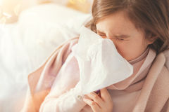Sick girl covering her nose with paper serviette. Be healthy. Little girl closing eyes and wrinkling forehead while blowing her nose Royalty Free Stock Photography
