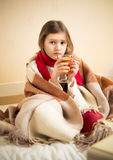 Sick girl covering in plaid and holding cup of tea Royalty Free Stock Images