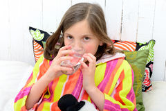 A sick girl drinking a glass of water Stock Photos