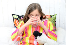 A sick girl drinking a glass of water Royalty Free Stock Photos